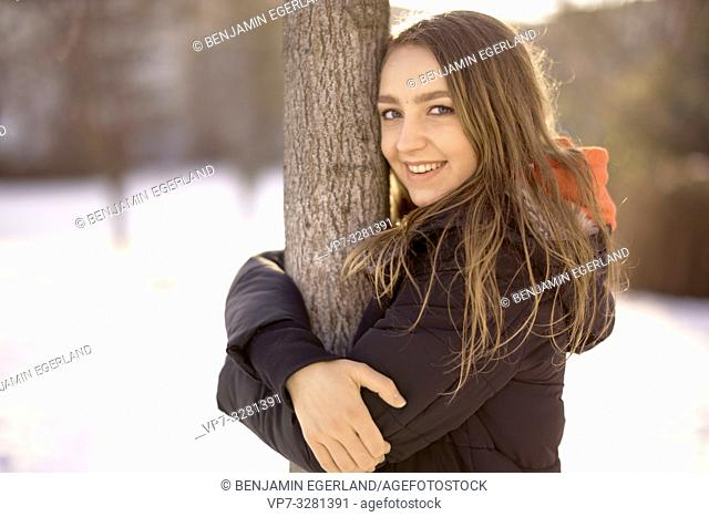 young woman embracing tree in nature, winter season, smiling, in Cottbus, Brandenburg, Germany