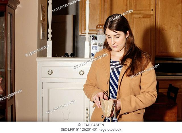Young woman looking into her purse