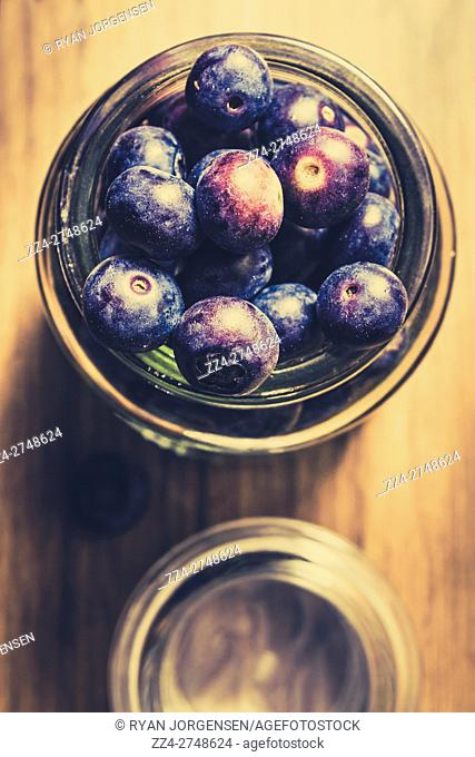 Top down view with vintage toning of freshly picked harvest of ripe blueberries in a jar on a wooden table with the lid alongside in a nutrition