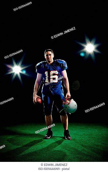 Portrait of american footballer holding helmet