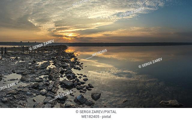 The shore of a drying lake in the rays of a colorful sunset