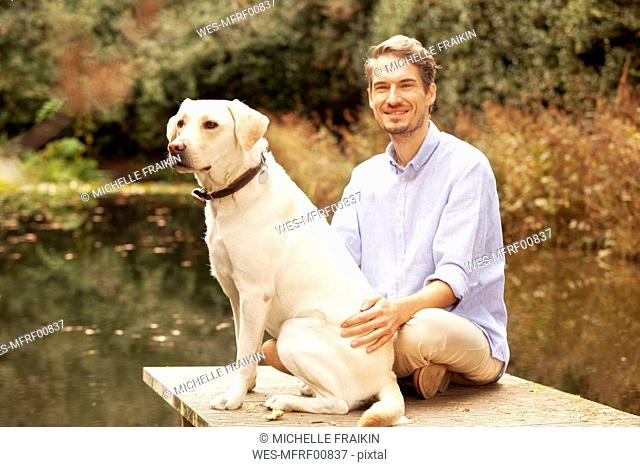 Man with dog on a jetty at a pond in autumn