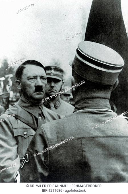 Adolf Hitler consecrating new flags with the Blutfahne blood flag, behind him chief of staff Viktor Lutze, historical photo between 1933-1943