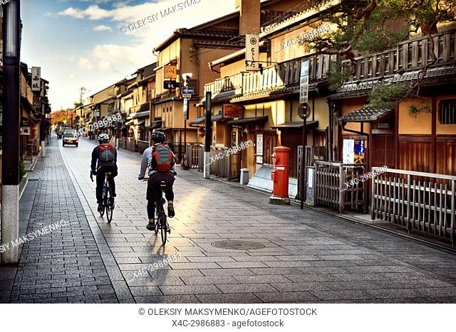 Cyclists on an empty Hanamikoji Dori street in Gion district in morning sunrise before all the shops and restaurants start opening