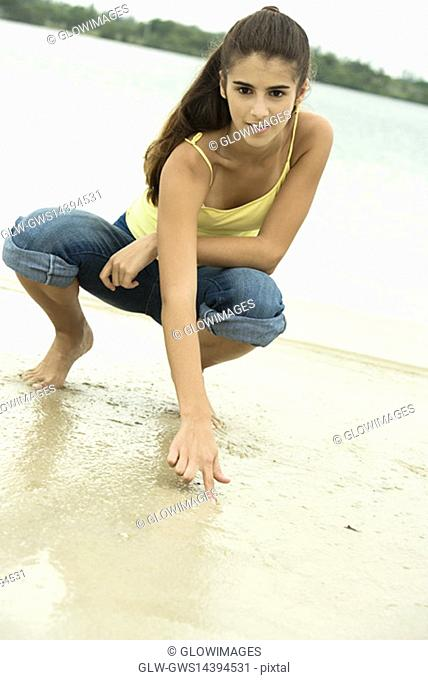 Portrait of a girl writing in sand with her finger