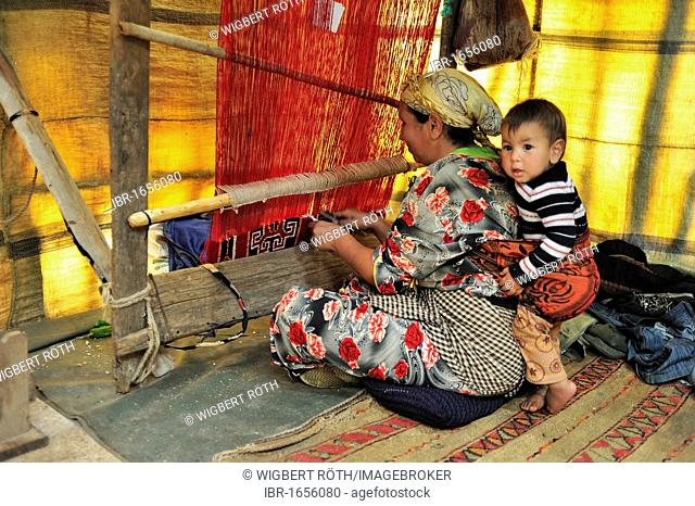 Berber woman working with a toddler in a sling on her loom, Middle Atlas, Morocco, Africa