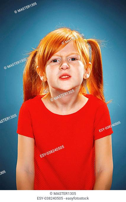 The beautiful portrait of displeased and disaffected little girl in red dress on blue