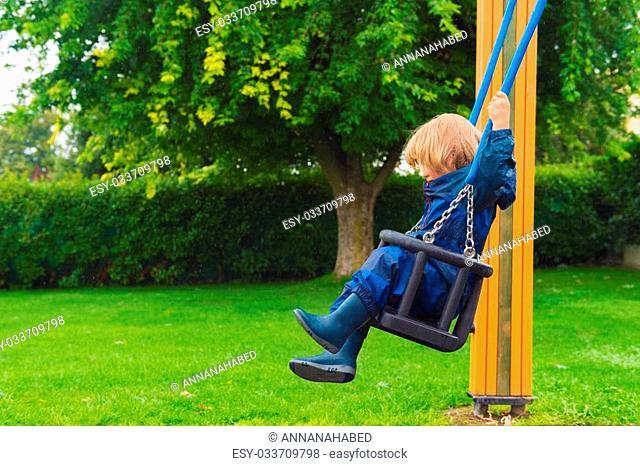 Cute little boy having fun on a swing on a rainy day, wearing blue waterpoof all-in-one suit