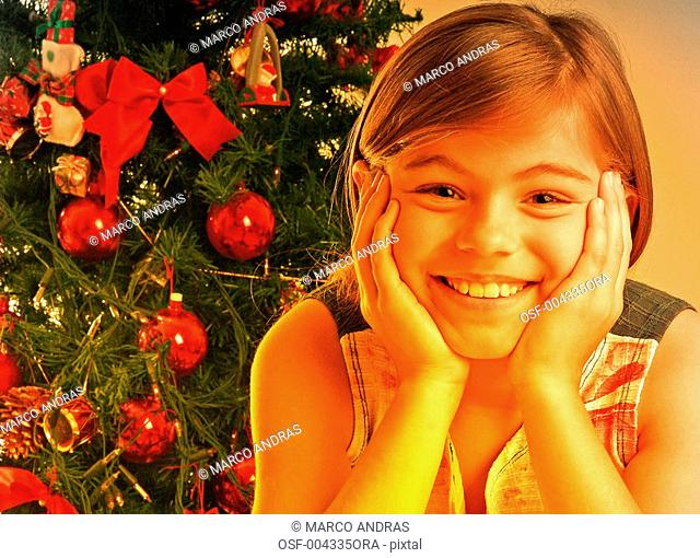 happy smiling child standing near a christmas tree