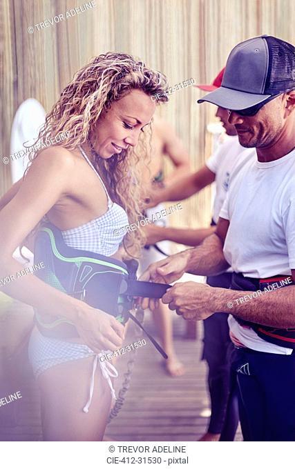 Man fastening kiteboarding safety harness on woman