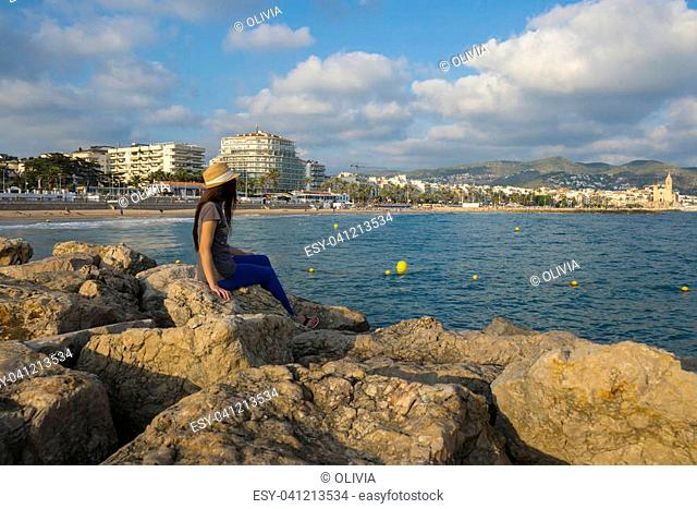 Sitges, Barcelona, Spain - October 01, 2016: The woman on a pier looks at the city of Sitges