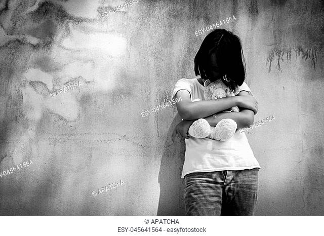 sad asian girl alone with white bear near old wall cement,Teen problem,women sorrow, black and white tone