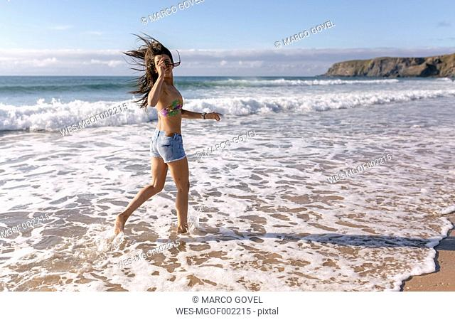 Spain, Asturias, beautiful young woman running on the beach