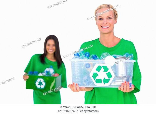 Pretty enivromental activists holding box of recyclables and smiling on white background