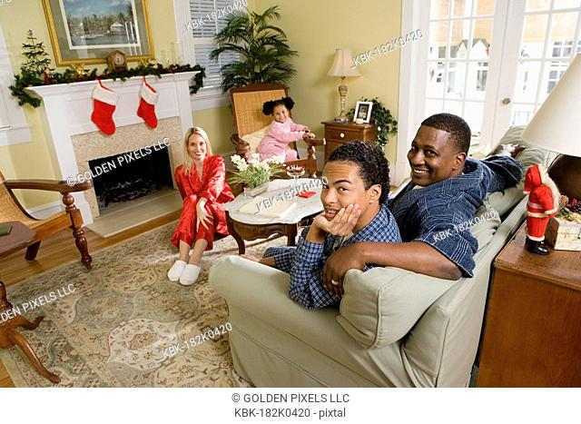 Family in pajamas sitting in living room decorated for Christmas