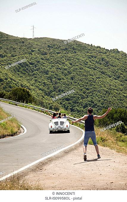 Convertible car driving past hitchhiker