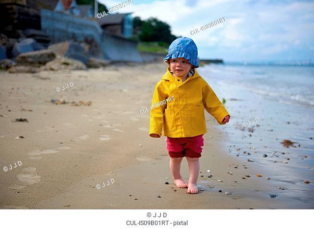 Baby girl on beach wearing sunhat and raincoat