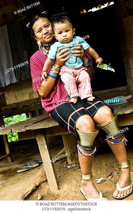 Portrait of a Gayo (Kayaw) Karen woman holding her child.photo taken in their small refugee village on the Thai / Burmese border