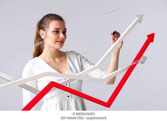Young businesswoman working with growth graph. Financial business concept on grey background