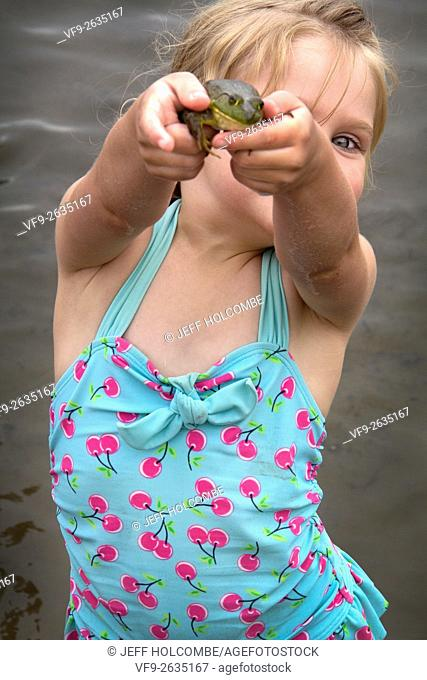 Little girl holding up a frog, peering out from behind with one eye, standing in a lake wearing a blue swimsuit
