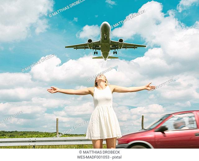 Car and plane behind young woman stretching out her arms