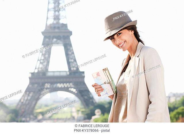 Woman holding a postcard with the Eiffel Tower in the background, Paris, Ile-de-France, France