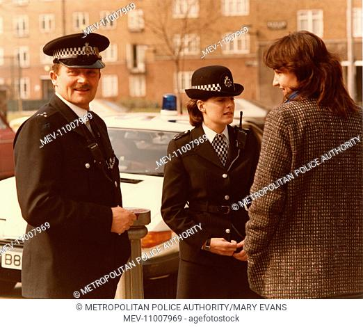 Male and female police officers in a London street, speaking to a young woman in a tweed jacket. The WPC is wearing the reinforced bowler hat introduced in 1985