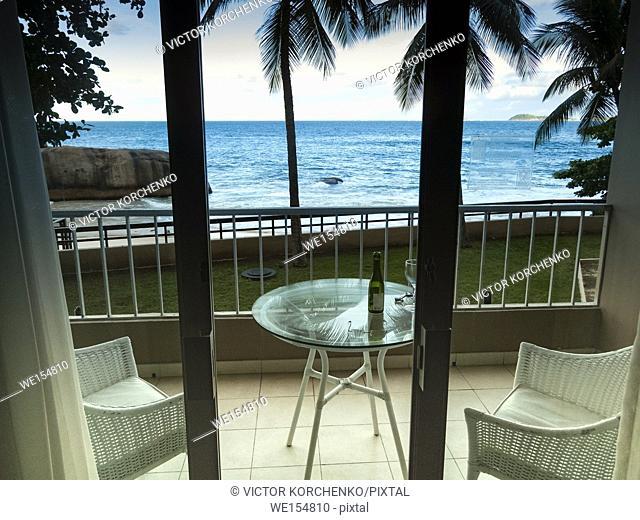 Hotel balcony overlooking ocean and palm trees in Rio de Janeiro