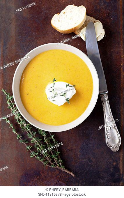 Pumpkin soup with sour cream, thyme and bread