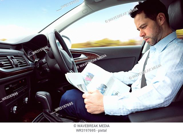 Businessman reading newspaper in a car