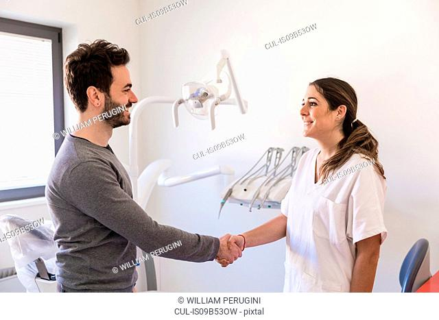 Female dentist shaking hands with patient in dental office