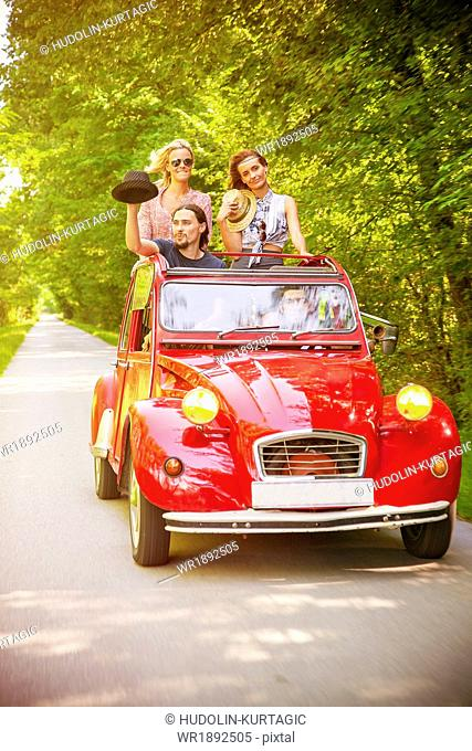 Young people in red vintage car having fun