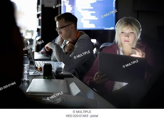 Focused female hacker working hackathon with laptop and headphones