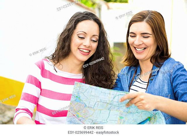Two beautiful female tourists searching a place on the map