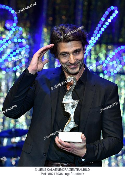 Italian actor Daniele Liotti poses with his award at theItalian film ball 'Notte delle Stelle' held during the 67th International Berlin Film Festival