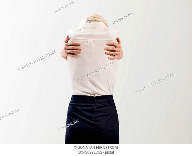 Woman embracing self, studio shot