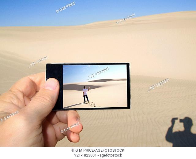 puzzling image of man photographing image on mobile digital device