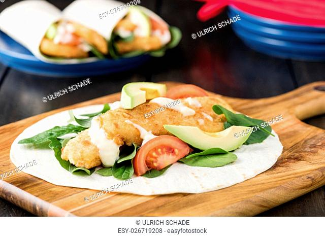 Crumbed fish fillet burrito with avocado and tomato serves on wooden cheese platter with rustic background