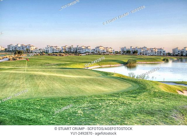 18th Green, fairway and water hazard with apartment in the distance at Hacienda Riquelme Golf Resort