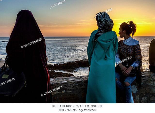 Young Moroccan People Watch The Sunset From A Popular Viewpoint In The Coastal Resort Of Asilah, Morocco