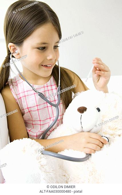 Little girl listening to teddy's bear's heart with stethoscope, looking at thermometer