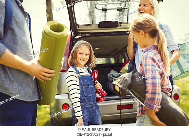 Portrait smiling girl with family unloading camping equipment from car