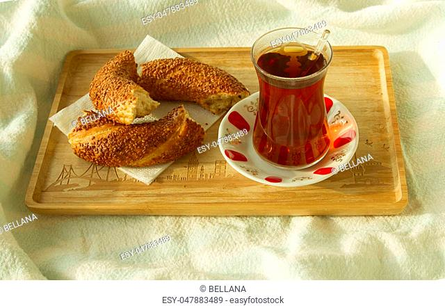 Bagel and cup of turkish tea on the wood tray with Istanbul picture on the bedcover