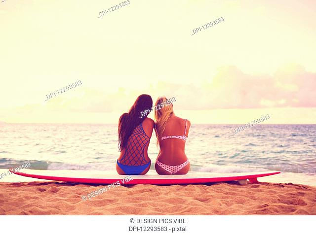 Surfer Girls On The Beach At Sunset. Summer Outdoor Lifestyle. Best Friends Hanging Out On The Beach