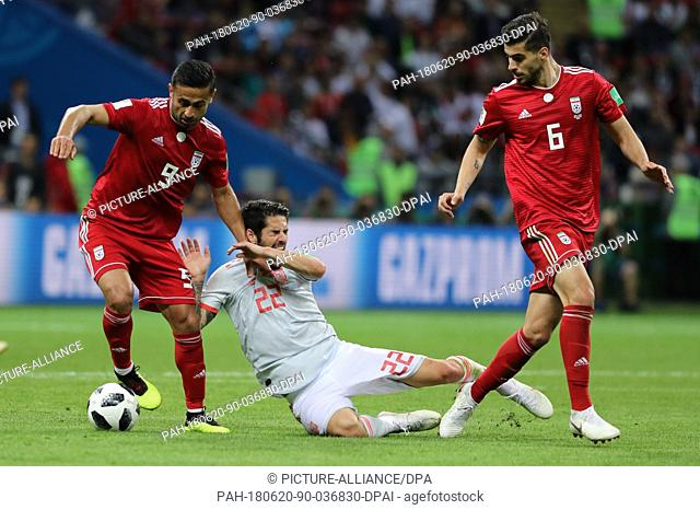 Iran's Omid Ebrahimi (L) and Saeid Ezatolahi in action against Spain's Isco during FIFA World Cup 2018 Group B soccer match between Iran and Spain at the Kazan...
