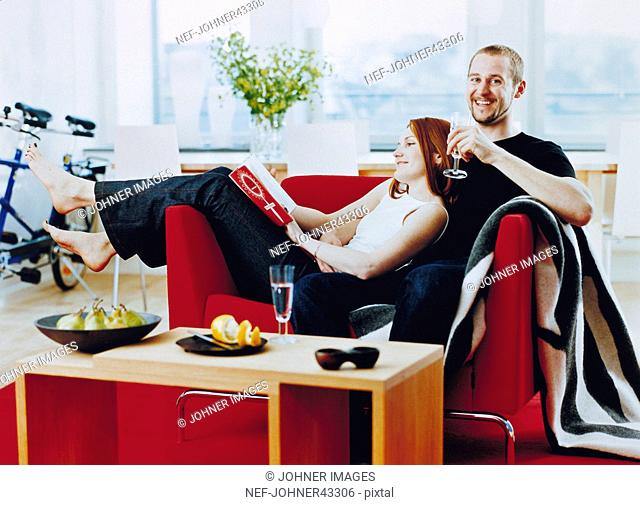 Man sitting on the couch with the woman in his lap reading a newspaper