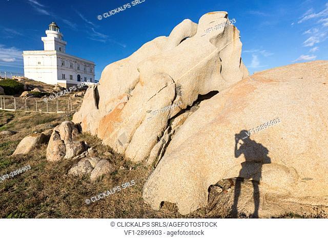 A silhouette is reflected on rocks next to lighthouse Capo Testa Santa Teresa di Gallura Sassari Province Sardinia Italy Europe
