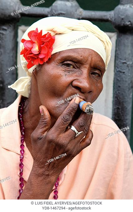 Morena woman smoking cigar black woman representative to the Cuban typical of the time in Old Havana, Cuba