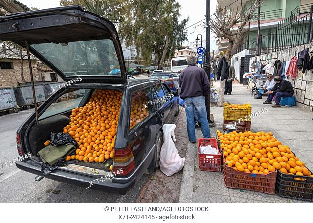 Selling oranges from the back of a Mercedes at a street market in Saranda, Southern Albania