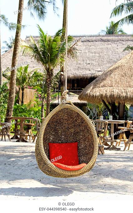 Wicker swing with a red pillow hanging on a coconut palm next to the sea on the sand beach. Island Koh Kood, Thailand. Close up